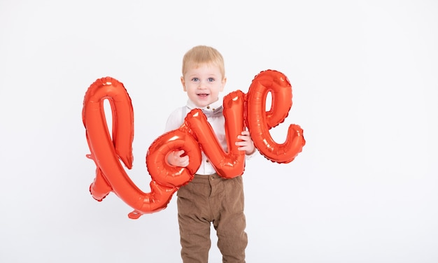 Il neonato del bambino in vestito tiene l'amore dell'iscrizione dai palloncini su una parete bianca.