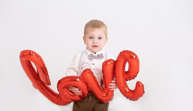 Il neonato del bambino in vestito tiene l'amore dell'iscrizione dai palloncini su un bianco.