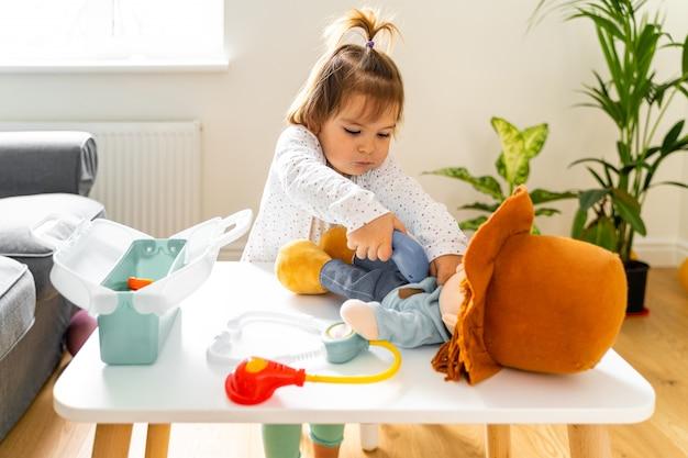 Ragazza del bambino del bambino che gioca con i giocattoli del kit e della bambola del medico