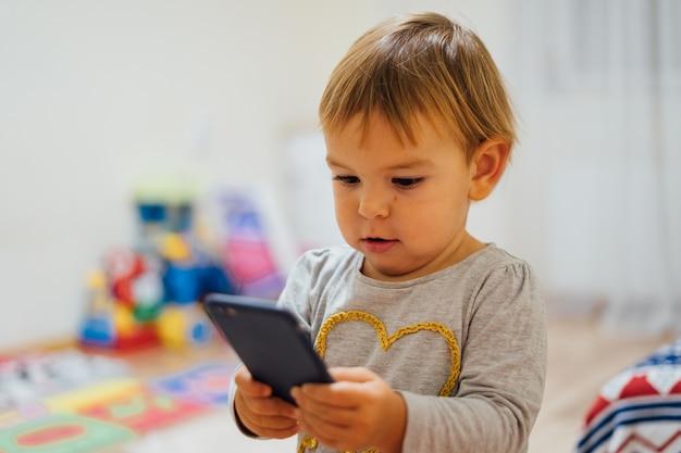 Bambino usando il telefono, giocando o guardando i cartoni animati. casa al chiuso. tempo dello schermo