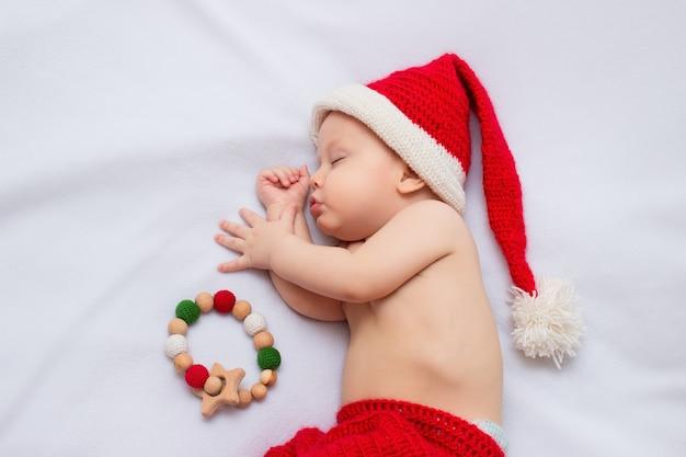 Bambino che indossa cappello e pantaloni da elfo natalizio rosso lavorato a mano all'uncinetto, dormendo su una coperta in pile bianco con un giocattolo sensoriale per la dentizione in legno con perline all'uncinetto