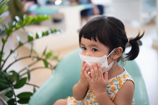 Bambino che indossa una maschera chirurgica seduto sul tavolo in ospedale