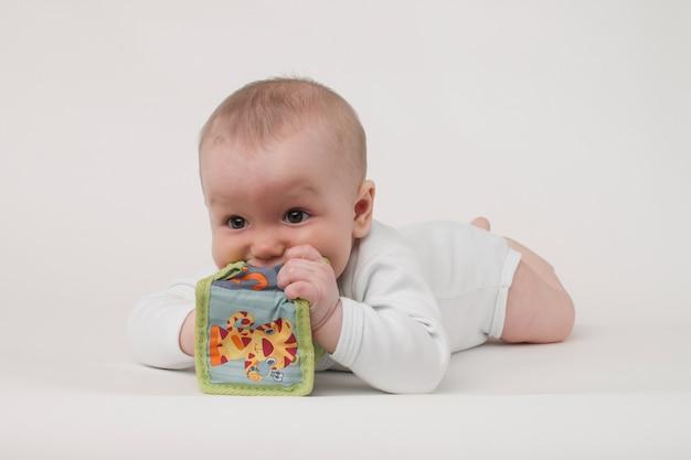 Bambino su uno sfondo bianco in un pigiama bianco con cubo giocattolo