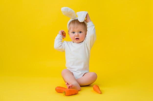 Il bambino in un body bianco con orecchie di coniglio in testa mangia carote, si siede su uno sfondo giallo con verdure. bambino sotto forma di un coniglietto di pasqua, spazio per il testo