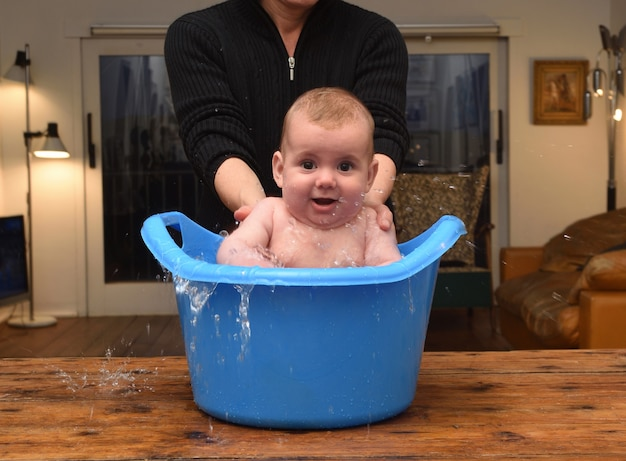 Bambino che fa il bagno in un secchio a casa