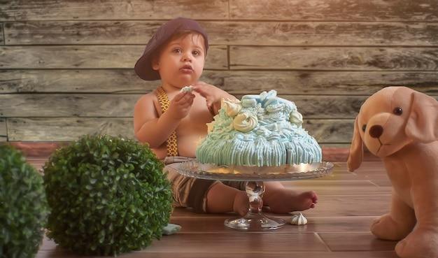 Bambino con torta di compleanno in un ritratto da set fotografico