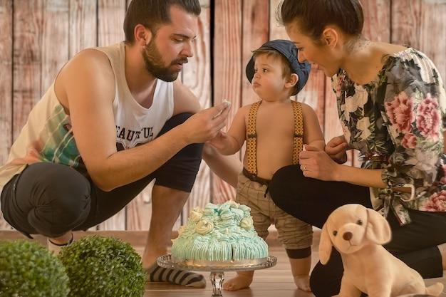 Bambino con torta di compleanno in un set fotografico con mamma e papà