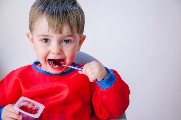 Bambino con un'espressione divertente che tiene un cucchiaio con gelatina. stile di vita familiare e dietetico.