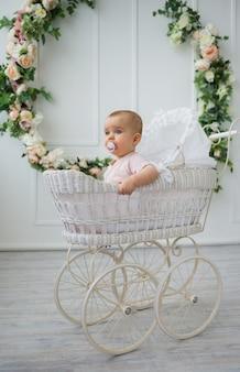 Il bambino con un ciuccio si siede in un passeggino retrò su uno sfondo bianco con fiori