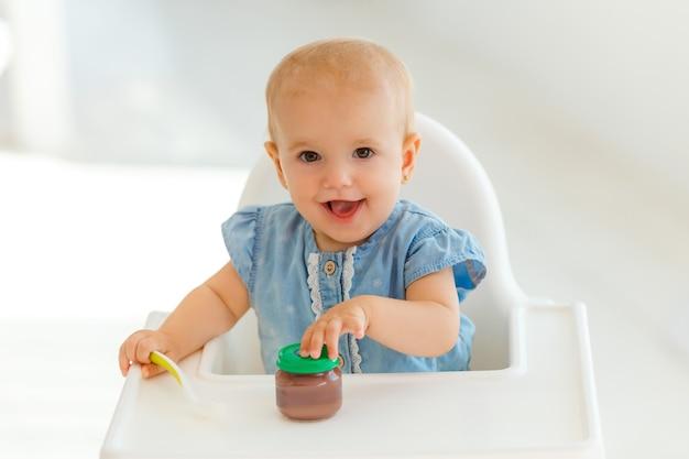 Bambino con il cucchiaio in mano mangiando purea di frutta nutrizione bambini. bambina seduta sul tavolo di alimentazione