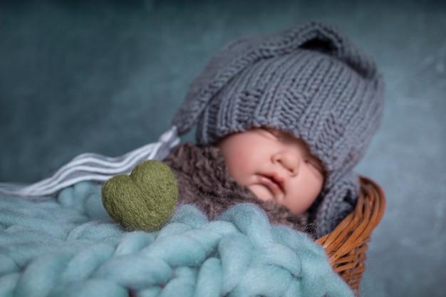 Bambino con berretto che dorme nel letto sfondo blu amore del bambino cuore verde