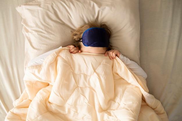 Il bambino si è svegliato e non voleva alzarsi dal letto ha gettato una coperta sulla testa nascondendosi
