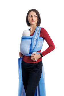 Babywearing attraente giovane madre con bambino nel marsupio intrecciato mani libere e attive