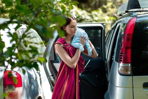 Babywearing giovane madre tira il suo bambino fuori dall'auto per metterlo in una fascia ad anello per una passeggiata