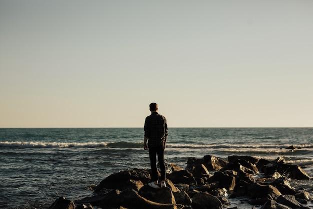 Dietro l'uomo solo e pensieroso sulla spiaggia. uomo che cammina alle pietre.