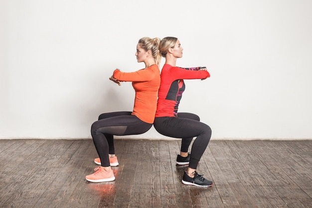 Pose di schiena contro schiena. amici che fanno esercizio di pilates. scatti in studio
