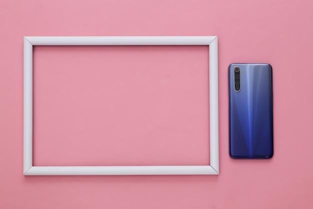 La cover posteriore di uno smartphone moderno con lenti su rosa con cornice bianca per il tuo testo