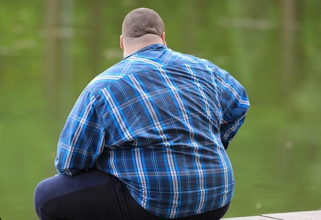 Uomo grasso di schiena con una camicia blu