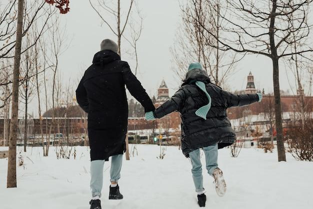 Indietro di felice coppia giovane corre mano nella mano nel parco invernale