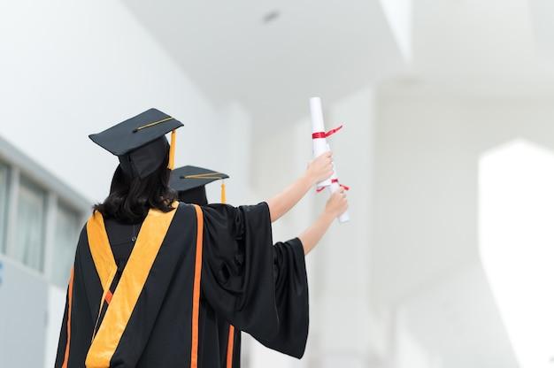 L'immagine posteriore di una studentessa universitaria laureata che indossa una nappa gialla cappello nero
