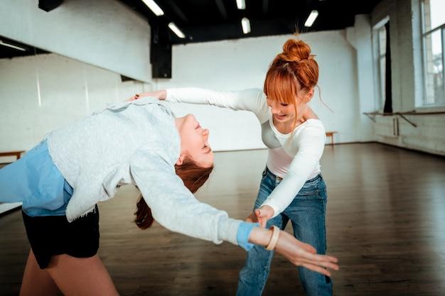 Appoggiarsi alla schiena. adolescente dai capelli lunghi che indossa pantaloncini neri praticando appoggiandosi alla scuola di danza