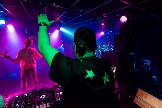 Indietro di un maschio dj con una mano sollevata in cuffia in un concerto elettronico