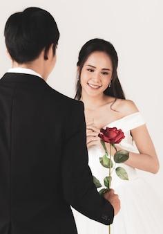 Retro dell'uomo che indossa uno smoking nero che dà rosa a una giovane donna asiatica attraente, presto sposa e sposo, donna che indossa abito da sposa bianco. concetto per la fotografia prematrimoniale.