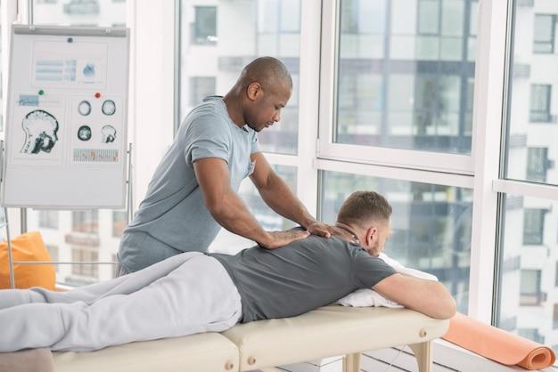 Massaggio alla schiena. bel uomo forte in piedi vicino al suo paziente mentre gli massaggia la schiena