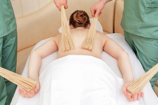 Massaggio alla schiena con scope di bambù a quattro mani.