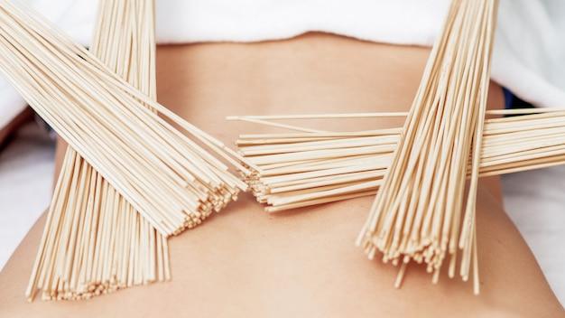 Massaggio alla schiena con scope di bambù