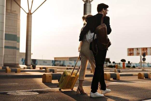 Foto posteriore di un uomo brunetta in abito nero e una donna in camicetta bianca, pantaloni beige si muovono vicino all'aeroporto e si abbracciano