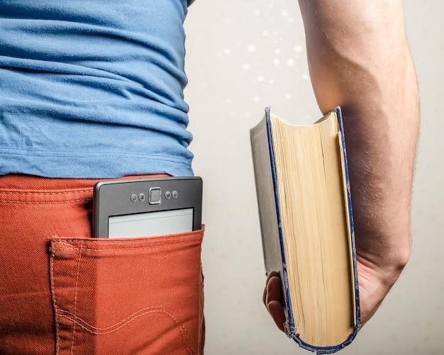 Nella tasca posteriore dei jeans c'è un e-book e nel libro di carte a mano dell'uomo