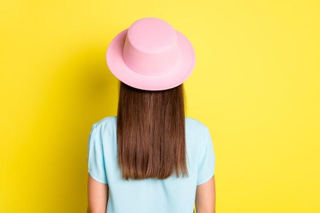 Vista posteriore della colonna vertebrale posteriore foto di una ragazza turistica che indossa un bel vestito estivo con cappello rosa t-shirt isolata su uno sfondo di colore vivido