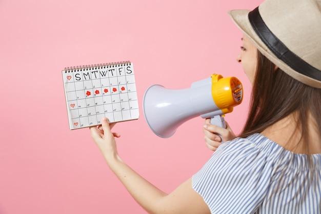 Vista posteriore della donna arrabbiata che urla nel megafono, tenendo il calendario dei periodi per controllare i giorni delle mestruazioni isolati su sfondo rosa. sanità medica, umore pms, concetto ginecologico. copia spazio.