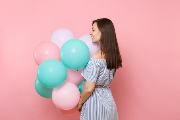 La retrovisione posteriore di bella giovane donna felice tenera in vestito blu tiene i palloni ad aria variopinti che guardano da parte isolati su fondo rosa luminoso. festa di compleanno, concetto di emozioni sincere della gente.