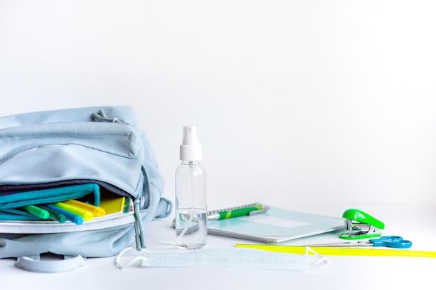 Ritorno a scuola dopo la pandemia di coronavirus. zaino, cancelleria, antisettico, maschera facciale su sfondo bianco.