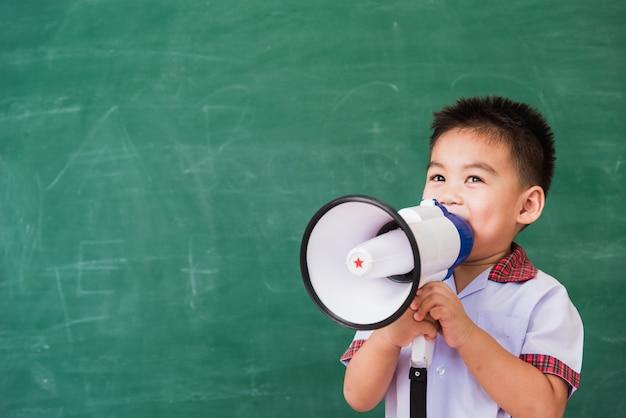 Di nuovo a scuola. asilo nido sveglio divertente asiatico del ragazzo del bambino piccolo in uniforme dello studente che parla tramite il megafono
