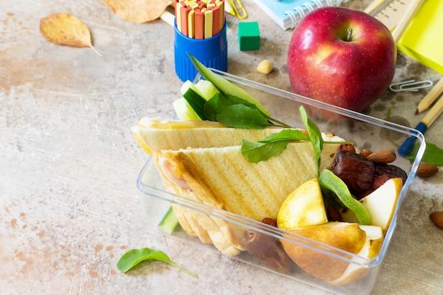 Ritorno allo sfondo della scuola pranzo scolastico mela e materiale scolastico copia spazio