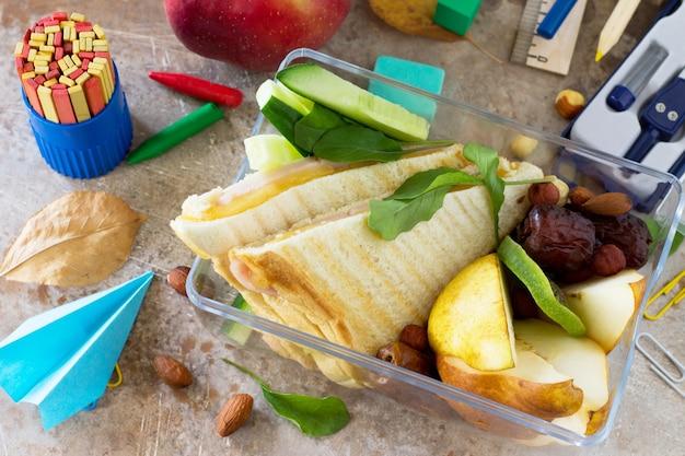 Ritorno allo sfondo della scuola scatola del pranzo della scuola mela e materiale scolastico aereo origami