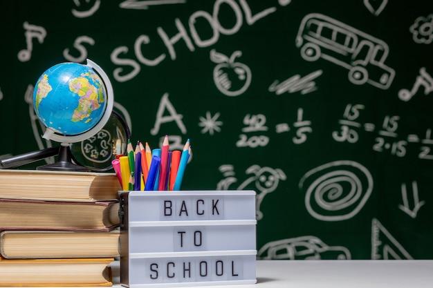 Ritorno a scuola con libri, matite e globo sul tavolo bianco su sfondo verde lavagna.