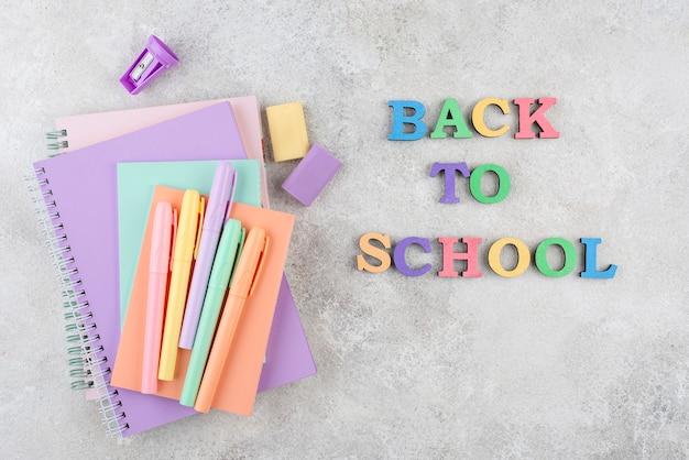 Torna a scuola sfondo con quaderni e penne colorate