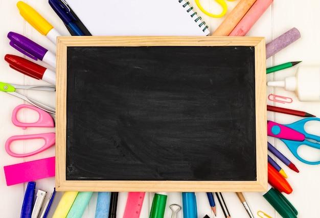 Torna a scuola lavagna nera su uno sfondo di legno bianco, forniture di colore. vista dall'alto. copyspace. concetto di educazione.