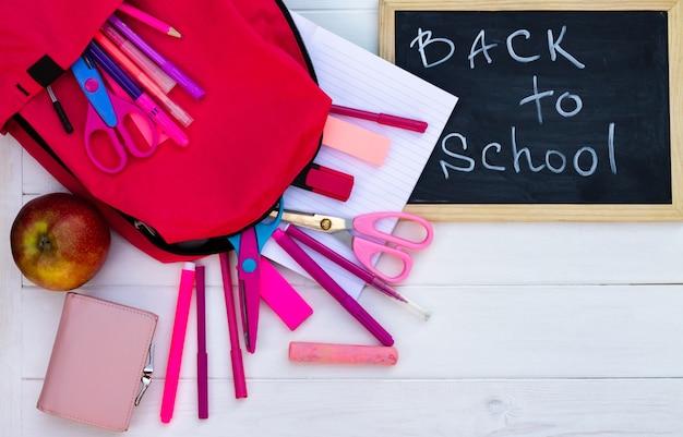 Torna a scuola lavagna nera su uno sfondo di legno bianco, forniture rosa. vista dall'alto. copia spazio. concetto di educazione.