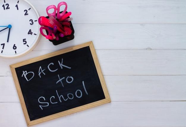 Torna a scuola lavagna nera su uno sfondo di legno bianco, forniture rosa. vista dall'alto. copyspace. concetto di educazione.