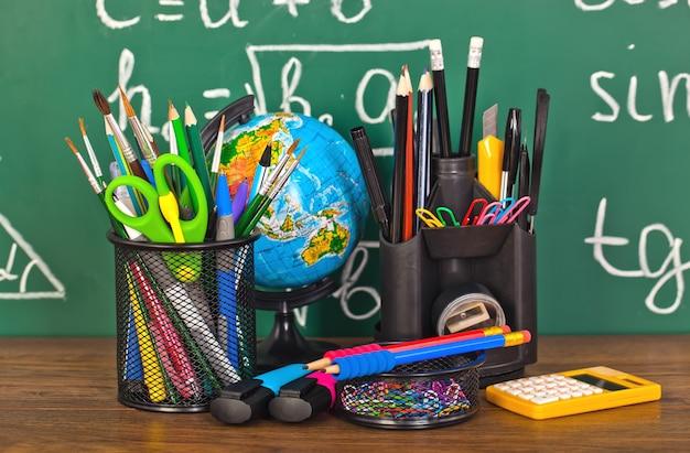 Ritorno a scuola - lavagna con astuccio e attrezzatura scolastica sul tavolo