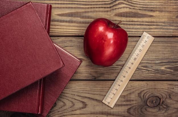 Di nuovo a scuola. libri, righello, mela rossa su un tavolo di legno. concetto di educazione