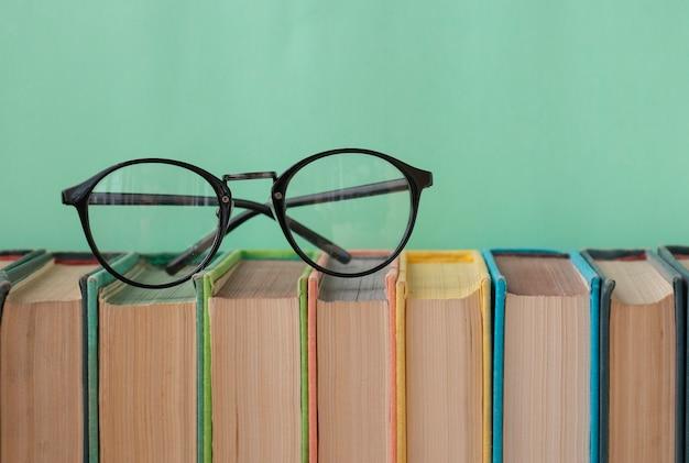Torna a libri di scuola per studio occhiali rotondi su uno sfondo verde chiaro