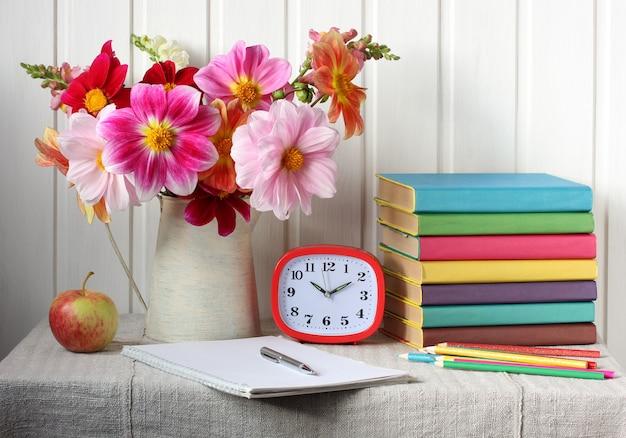 Di nuovo a scuola. bouquet di dalie e libri di testo.