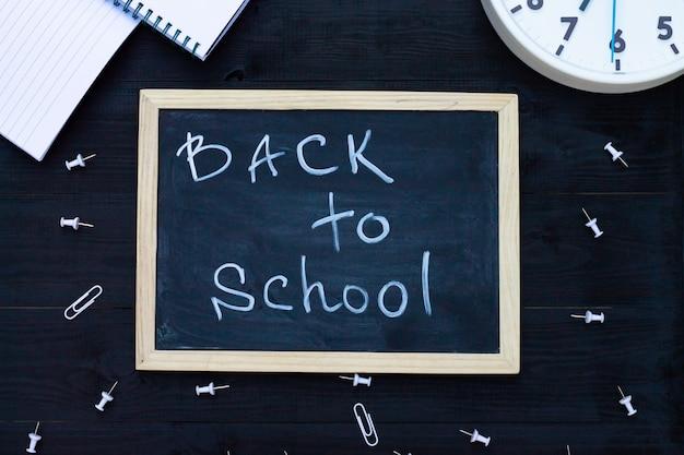 Torna a scuola lavagna su uno sfondo di legno nero, forniture bianche, orologio. vista dall'alto. copyspace. concetto di educazione.