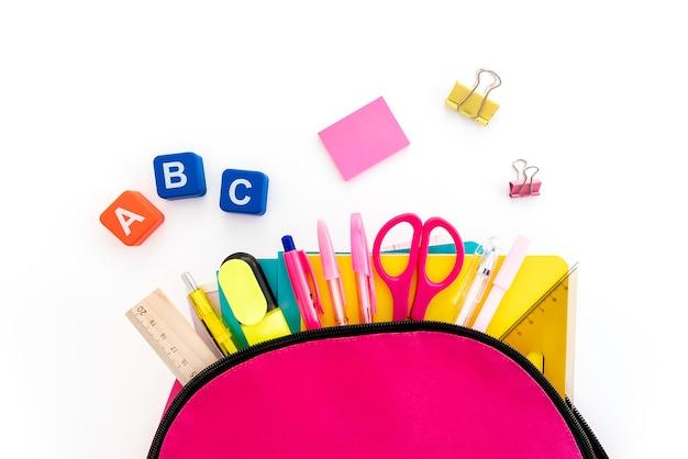 Torna al concetto di scuola. zaino con materiale scolastico su bianco